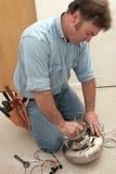 L'électricien assemble le moteur de ventilateur Photographie stock