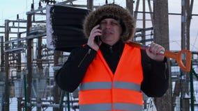 L'électricien avec le téléphone intelligent et la neige pellent aux centrales en hiver clips vidéos