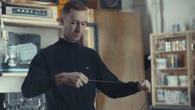 L'électricien dans son atelier tord les fils noirs pour rendre élém. élect. Photographie stock