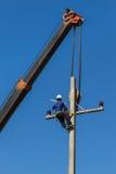 L'électricien installent le fil de la ligne électrique avec la grue Image stock