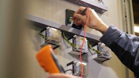 L'électricien mesure le courant utilisant le mètre électrique combiné banque de vidéos