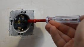 L'électricien principal examine la tension dans la prise avec un multimètre pendant la réparation et l'installation banque de vidéos