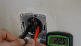 L'électricien principal examine la tension dans la prise avec un multimètre pendant la réparation et l'installation clips vidéos