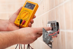 L'électricien remet vérifier la tension dans un électrique partiellement monté Photo libre de droits