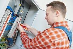 L'électricien travaille avec le tournevis dans la boîte de fusible Image libre de droits
