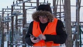 L'électricien a utilisé la tablette aux centrales en hiver banque de vidéos