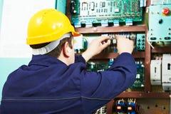 L'électronique adulte d'essai de travailleur d'ingénieur de constructeur d'électricien dans le panneau de commutateur Photographie stock