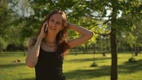 L'élever de sourire de jeune femme au parc dehors parlent par le téléphone banque de vidéos