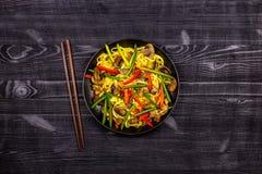 L'?moi app?tissant a fait frire des nouilles avec des pousses d'ail, des champignons, le poivron rouge et la viande de poulet sur image stock