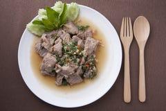L'émoi de porc a fait frire dans le plat blanc avec la cuillère et la fourchette en bois Photos libres de droits