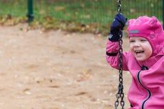 L'émotion de l'enfant sur le terrain de jeu dans le jour d'automne photos stock