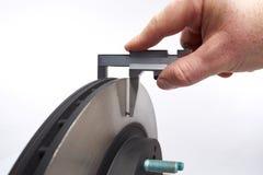 L'épaisseur de disque de frein de voiture a mesuré en en largeur avec un Han Photos libres de droits