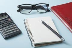 L'épargne à la maison, concept de budget Calculatrice, stylo et livres de comptes sur la table de bureau photographie stock