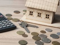 L'épargne à la maison, concept de budget Maison modèle, clés, calculatrice et pièces de monnaie sur la table en bois de bureau Photo stock