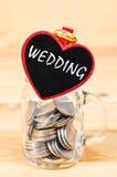 L'épargne en anneau en verre de banque et de mariage Image libre de droits