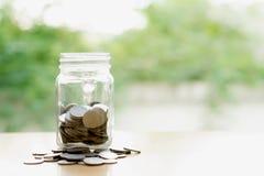 L'épargne exprime avec la pièce de monnaie d'argent dans le pot en verre financier photographie stock