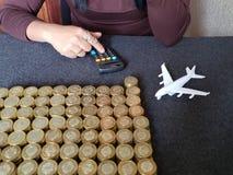 l'épargne pour le voyage, la main d'une femme dans la calculatrice, la figure d'un avion blanc et les pièces de monnaie empilées  photo libre de droits