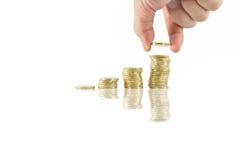 L'épargne se ferme de la main masculine empilant les pièces de monnaie d'or sur le fond blanc Photographie stock