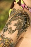 L'épaule de la femme tatouée. Image stock