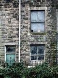 L'épave a abandonné la maison avec les fenêtres cassées et le lierre grandissant Image libre de droits