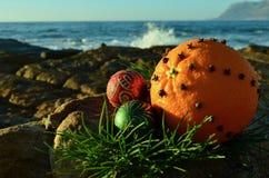 L'épice de clou de girofle de Noël a cloué le fruit orange sur Noël rouge et vert de roche de scintillement de décorations en jui images stock