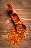 L'épice de safran filète dans le scoop sur le fond en bois Photos libres de droits