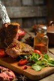L'épice froide a bouilli le porc avec des tomates sur la table en bois Photographie stock