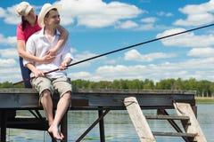 L'épouse étreint son mari sur la pêche quand il pêche des poissons Photographie stock