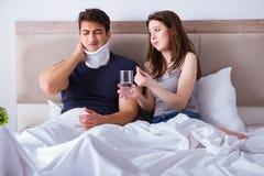 L'épouse affectueuse prenant soin de mari blessé dans le lit Photographie stock