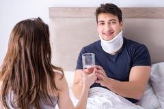 L'épouse affectueuse prenant soin de mari blessé dans le lit Photo stock