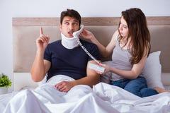 L'épouse affectueuse prenant soin de mari blessé dans le lit Image libre de droits