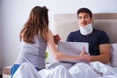L'épouse affectueuse prenant soin de mari blessé dans le lit Photographie stock libre de droits
