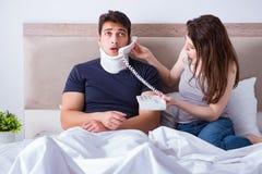 L'épouse affectueuse prenant soin de mari blessé dans le lit Image stock
