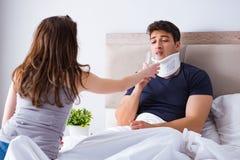 L'épouse affectueuse prenant soin de mari blessé dans le lit Images libres de droits