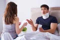 L'épouse affectueuse prenant soin de mari blessé dans le lit Photos libres de droits