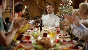 L'épouse donne le cadeau de Noël à son mari pendant le dîner de famille clips vidéos