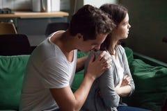 L'épouse irritée de présentation d'excuses de mari disant excuser désolé pour soit image libre de droits