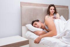 L'épouse lisant ses maris textotent des messages de sms Image libre de droits