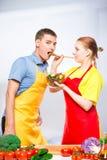 l'épouse traite un homme avec de la salade de légume frais, une paire de tabliers photos libres de droits