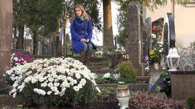 L'épouse triste de femme s'asseyent sur le banc dans le cimetière de ville dans le temps d'automne 4K clips vidéos