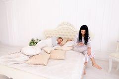 L'épouse vérifie moyennement son téléphone du ` s de mari, alors qu'il dort Photo stock