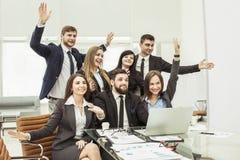 L'équipe d'affaires avec leurs mains se lèvent et votant pour la prise de décision près du bureau Photographie stock libre de droits