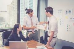 L'équipe d'affaires ayant une réunion utilisant l'ordinateur portable au cours d'une réunion et les présents profitent avec le di Image stock