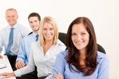 L'équipe d'affaires heureuse s'asseyent dans la ligne derrière la table Photographie stock libre de droits