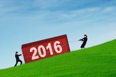 L'équipe d'affaires portent un bloc avec les numéros 2016 Photos libres de droits
