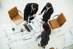 l'équipe d'affaires travaillant avec les graphiques financiers et discute le bénéfice de la société Photo stock