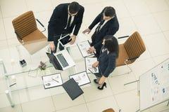l'équipe d'affaires travaillant avec les graphiques financiers et discute le bénéfice de la société Image stock