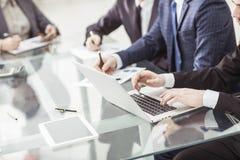 L'équipe d'affaires utilisant un ordinateur portable fait un rapport de vente sur le lieu de travail photo stock