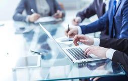 L'équipe d'affaires utilisant un ordinateur portable fait un rapport de vente sur le lieu de travail photographie stock