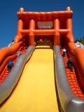 L'équipe d'enfants concurrencent dans la vitesse montant les glissières gonflables Image stock